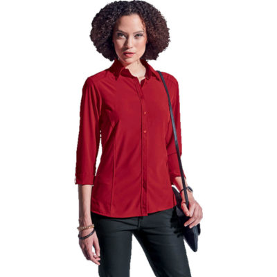 The Ladies Geneva Blouse is made from polyester spandex ultra-soft, stretch fabric in a red colour. Features include a two-piece collar with three quarter sleeves, half-concealed button stand, a flattering side panel cut, high-low hem with side slits and front & back yokes.