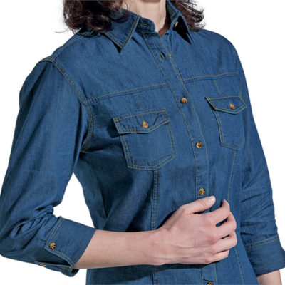 The Ladies Denver Denim Blouse made from 100% cotton fabric. The features include a shaped hem, two tone buttons, patch pocket with flaps at the chest, constructed button stand, contrast top stitching, double layer back yoke and turn up cuffs.