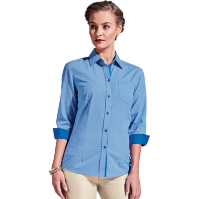 The Ladies Madison Blouse Is A Sky Blue Poly Cotton Dress shirt With Solid Contrasting Inserts On The Inner Collar Stand, Button Stand And Cuffs. Features Include Busts And Waist Darts, A Feminine Cut, Turn Up Cuffs, Contrast Inserts, Chest Pocket And 3/4 Sleeves