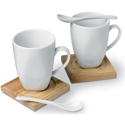 The Mug and Coaster Gift Set includes two ceramic mugs with matching spoons, and wooden coasters. This charming set is presented in an elegant black box.
