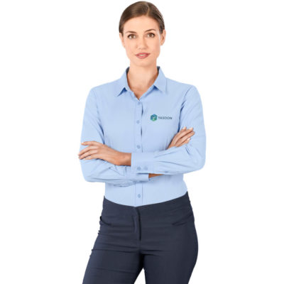 The Ladies Long Sleeve Nottingham Shirt is a blended fabric, long sleeve sky blue shirt with side slits. A curved hem and two button cuff detail on the sleeves. Front and back darts for shaping and a curved hem.
