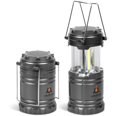 Swiss Cougar Speaker and lantern next to eachother. Both in cylindrical shapes with a gun metal colour and the lantern is taller with a handle.