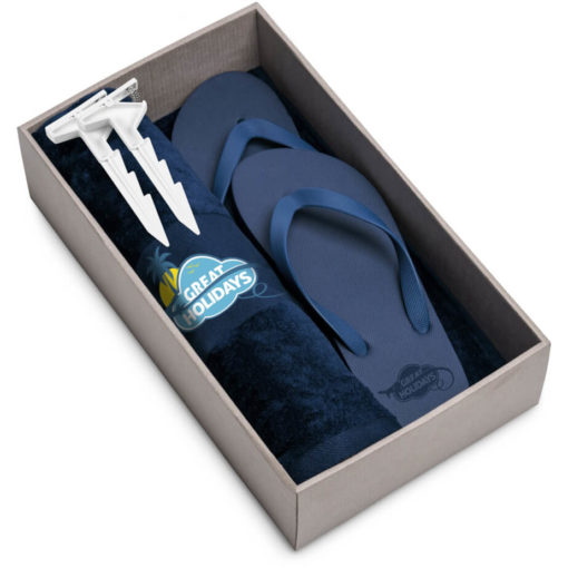 The Beach Break Summer Set includes a navy 100% cotton towel, navy EVA & PVC flip flops and a white plastic blanket clip. Packaged in a brown box