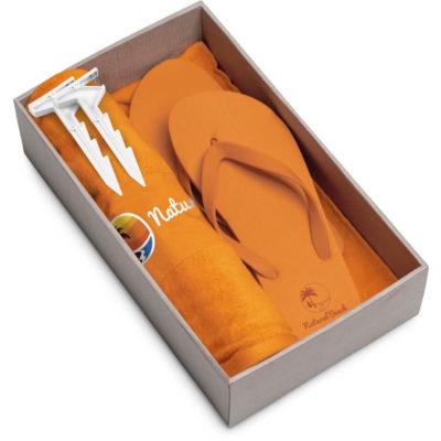 The Beach Break Summer Set includes a orange 100% cotton towel, orange EVA & PVC flip flops and a white plastic blanket clip. Packaged in a brown box