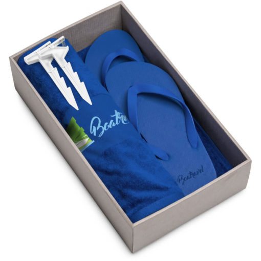 The Beach Break Summer Set includes a blue 100% cotton towel, blue EVA & PVC flip flops and a white plastic blanket clip. Packaged in a brown box