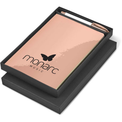 The Reflections Gift Set is a metalic rose gold notebook set that includes an A5 PU lamited with TPU cover notebook with 160 lined pages and a white iron barrel ball point pen with black ink and rose gold brass lid and trim. Packaged in a black presentatino gift box