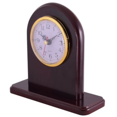 The Rosewood Desk Clock is a brown MDF rosewood desk clock with a flat base and rounded edge display face. Holds a circular clock with gold trim detail, intricate black arms, bold numbering for the hours and minute interval markings