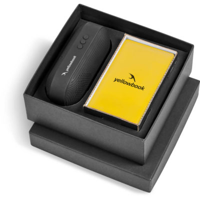 The Maxicon Gift Set contains a yellow 4000mAh slimline rectangular powerbank with a micro USB charging cable, and a black oval shaped Bluetooth speaker with a nylon wrist strap. Packaged in a black presentation gift box