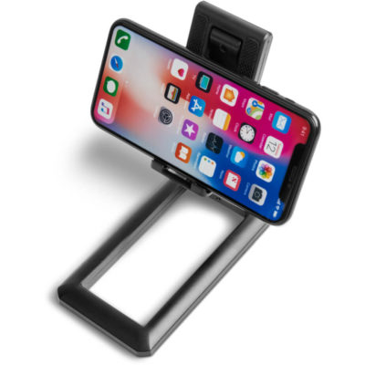 The Pronto Adjustable Phone Stand is a black ABS adjustable phone stand that folds flat when not in. With a shelf to hold your phone, spacing to insert your charging cable, adjustable height and angle frome and two rubber grips to hold your phone securely