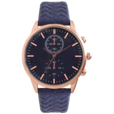 The Classic Woven Watch is a blue leatherette strap watch with a round rose gold trim face, hour and minute interval markers, pointed arms and a side knob to adjust the time and date